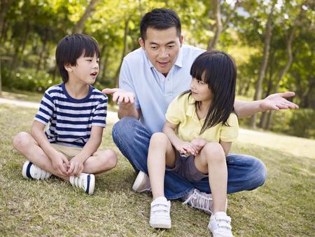 padres hablando con hijos: padre asiático y dos niños sentados en la hierba que tiene una conversación interesante, al aire libre en un parque. Foto de archivo