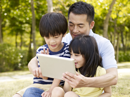 asian family: asian father and two children sitting on grass looking at tablet computer, outdoor in a park.