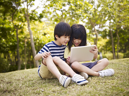 using: little asian girl and boy sitting on grass using digital tablet outdoors in a park.
