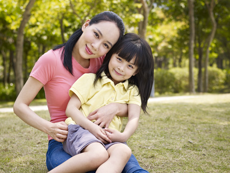 madre e hijos: madre asiática y su hija sentada en la hierba en un parque. Foto de archivo