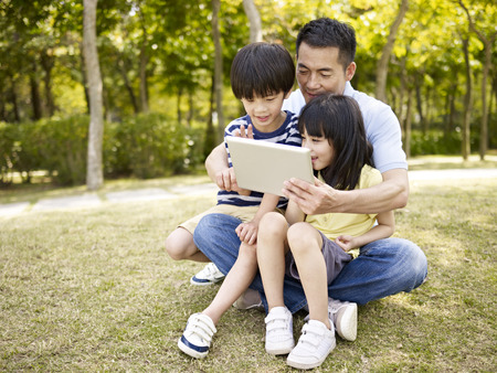 asian father and two children sitting on grass looking at tablet Stock Photo