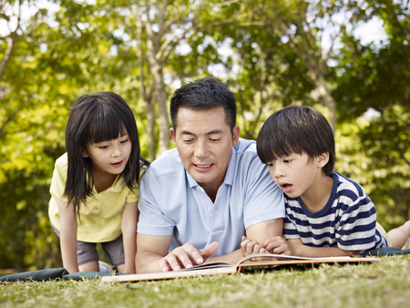 asian father and children lying on grass reading a book together in a park.