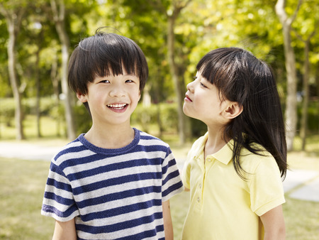 outdoor portrait of two playful asian children.