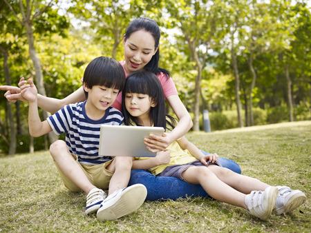 niñas jugando: madre asiática y dos niños que usan el ordenador tablilla al aire libre.