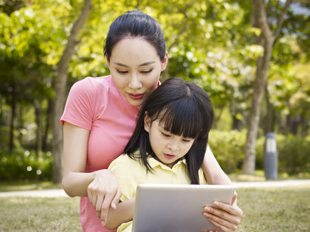 asia nature: asian mother and daughter using tablet outdoor Stock Photo