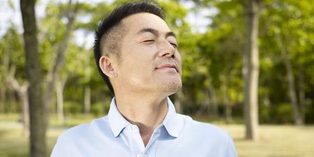 atmung: asiatischer Mann genießen einen Spaziergang und frische Luft in der Natur.