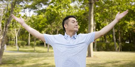 persona respirando: Hombre asiático disfruta de una caminata y el aire fresco en la naturaleza. Foto de archivo
