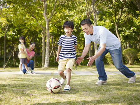 family on grass: asian father teaching son to play soccer (football) in a park