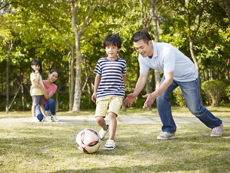 Aziatische vader onderwijs zoon naar voetbal (voetbal) spelen in een park Stockfoto
