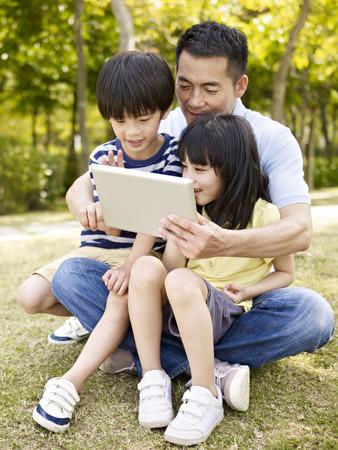 アジアの父と 2 人の子供を見ているタブレット コンピューター、屋外の公園で芝生の上に座っています。 写真素材 - 41975105