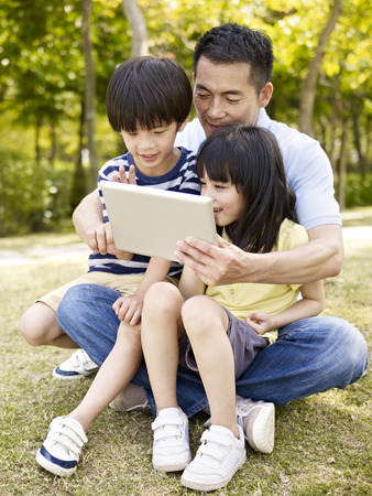 two story: asian father and two children sitting on grass looking at tablet computer, outdoor in a park.