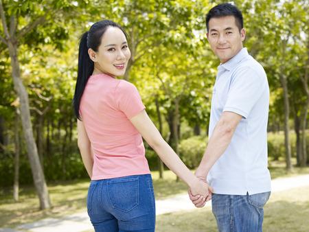 manos entrelazadas: joven pareja asiática de la mano caminando en el parque.