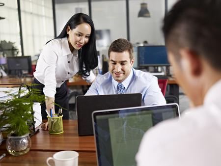 negocios internacionales: Hombres de negocios asiáticos y caucásicos trabajando juntos en la oficina de una empresa multinacional.