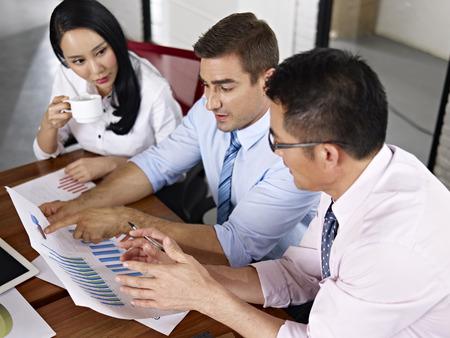 reunion de trabajo: ejecutivos de negocios asi�ticos y cauc�sicos de reuniones en la oficina de una empresa multinacional. Foto de archivo