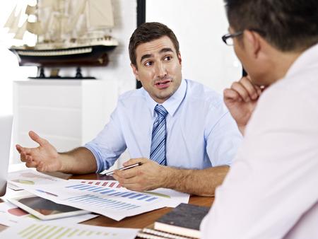 boss: ejecutivos de negocios asiáticos y caucásicos revisar y discutir el desempeño del negocio en la oficina de una empresa multinacional. Foto de archivo