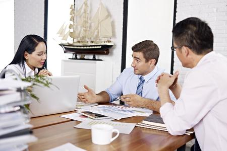 negocios internacionales: ejecutivos de negocios asiáticos y caucásicos revisar y discutir el desempeño del negocio en la oficina de una empresa multinacional. Foto de archivo