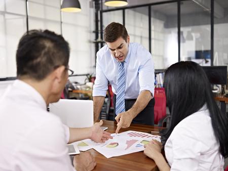 jefe enojado: dos ejecutivos de negocios asi�ticos que discuten con cauc�sico superior en la oficina de una empresa multinacional.