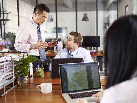 multinacional: empresarios asi�ticos y cauc�sicos tener una discusi�n en la oficina de una empresa multinacional.