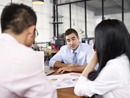 supervisores: dos ejecutivos de empresas asiáticas en discusiones sobre el rendimiento del negocio con caucásico superior en la oficina de una empresa multinacional.