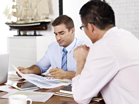 multinacional: ejecutivos de negocios asi�ticos y cauc�sicos revisar y discutir el desempe�o del negocio en la oficina de una empresa multinacional. Foto de archivo