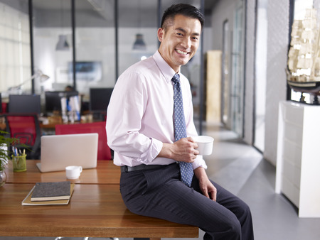 smiling businessman: an asian businessman holding cup of coffee sitting on desk in office, smiling and cheerful. Stock Photo