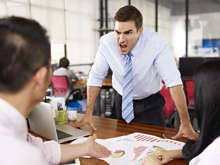 angry businessman: bad-tempered caucasian business executive yelling at two asian subordinates in office. Stock Photo