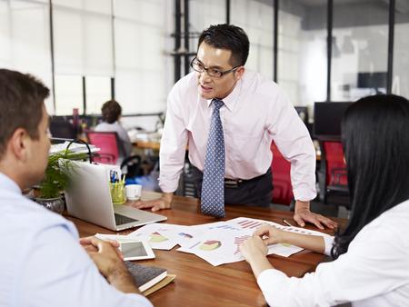 jefe enojado: malhumorado hombre de negocios asiático que grita en dos subordinados en el cargo. Foto de archivo