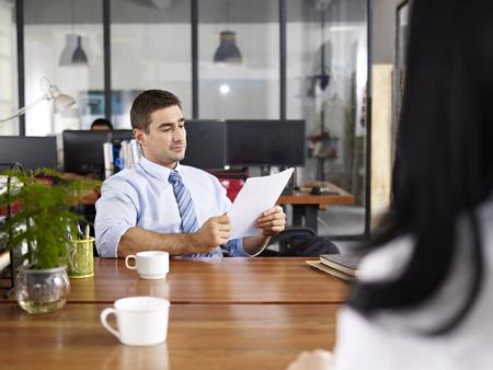 evaluacion: caucásico gerente de Recursos Humanos mirando una hoja de vida mientras entrevistaba a una candidata. Foto de archivo