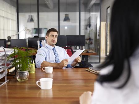 preguntando: caucásico gerente de Recursos Humanos mirando una candidata mujer durante una entrevista.