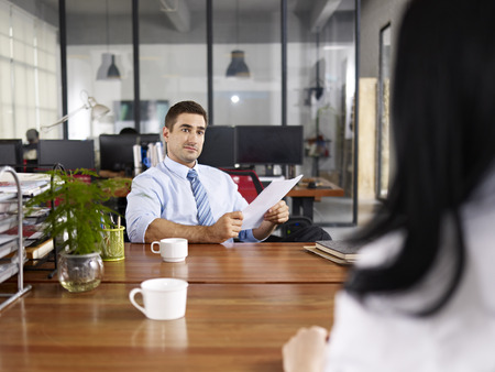 caucasian HR manager looking at a female candidate during an interview. Stock Photo
