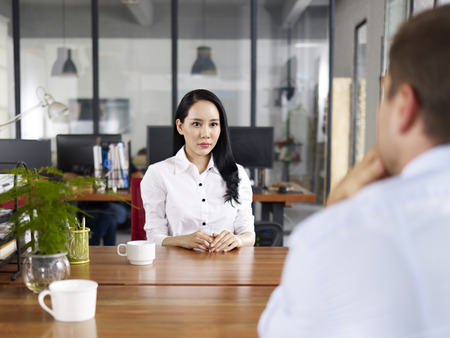 candidate: young asian businesswoman looking serious and nervous during a job interview. Stock Photo