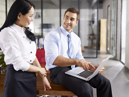 westerner: caucasian businessman pointing  to laptop screen while talking to his female asian coworker in office of a multinational company. Stock Photo