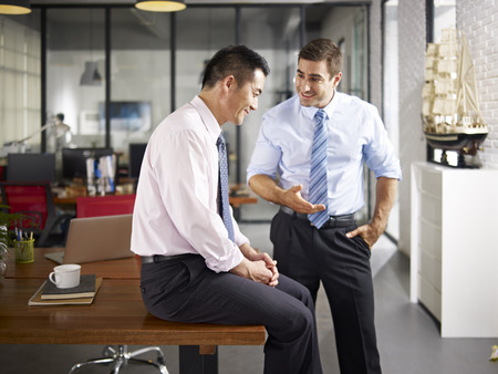 the good life: asian and caucasian businessmen enjoying a pleasant conversation in office of a multinational company.
