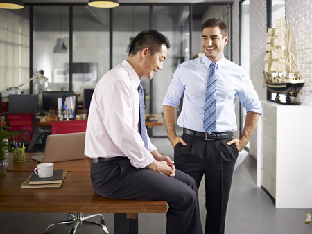 asian and caucasian business people talking and smiling in office of a multinational company.