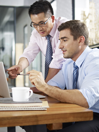 foreign: asian and caucasian business executives looking at laptop screen while having a discussion in a multinational company. Stock Photo