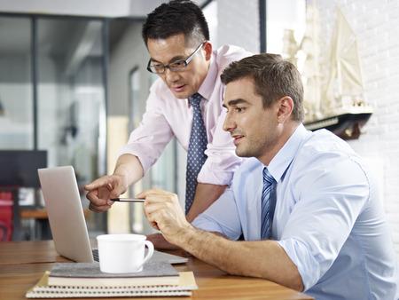 ejecutiva en oficina: asiáticos y caucásicos ejecutivos de negocios mirando la pantalla del ordenador portátil mientras que teniendo una discusión
