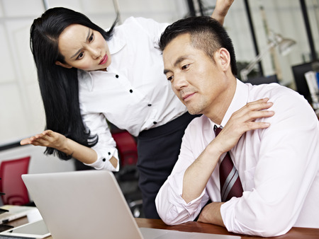 asian businesswoman: businesswoman puzzled and baffled at her male colleagues behavior.