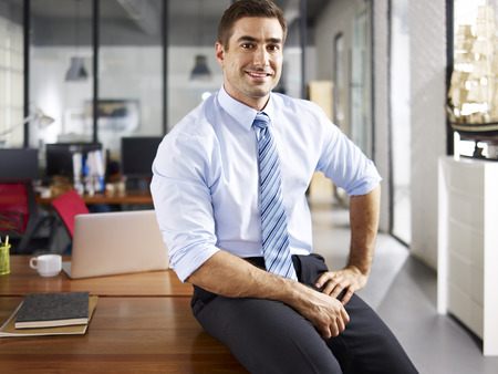 portrait of a smiling caucasian business executive sitting on desk in office.