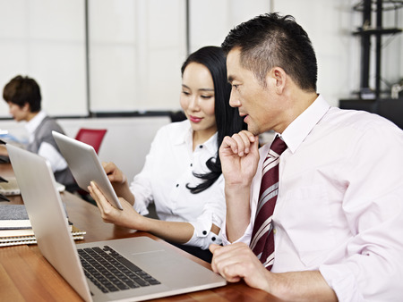 laptop computers: asian businesspeople discussing business in office with help of laptop and tablet computers.