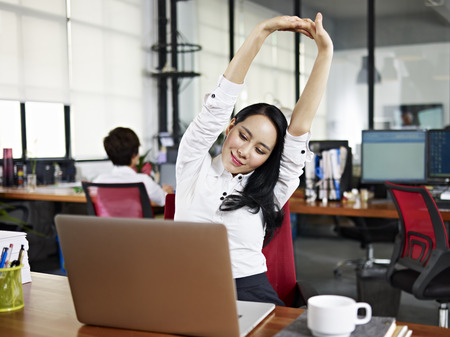 office break: asian businesswoman looking at work on laptop computer with satisfaction and stretching arms in the air.