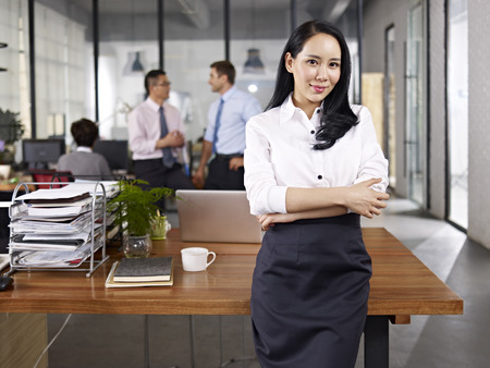 executive women: young asian businesswoman standing in office with multiethnic colleagues talking in background