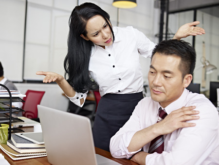 coworker: asian businesswoman puzzled and baffled at  male colleagues behavior.