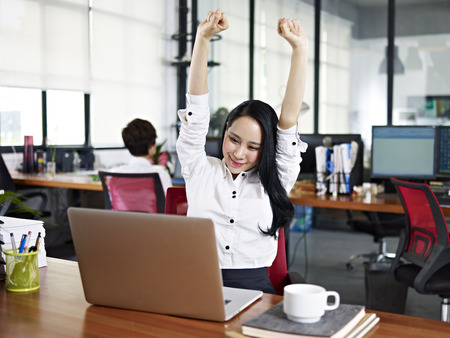 happy workers: asian businesswoman stretching arms in the air to celebrate completion of task.