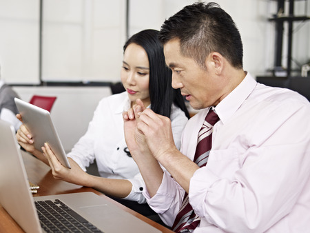 life partner: asian business man and woman looking at laptop and tablet computer having a discussion.