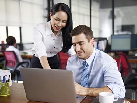 féminin employé de bureau travaillant ensemble avec son collègue dans le bureau caucasien expatriés.