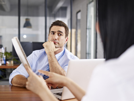 patron: un entrevistador masculino caucásico que mira escéptico mientras escucha un entrevistado femenino asiático.