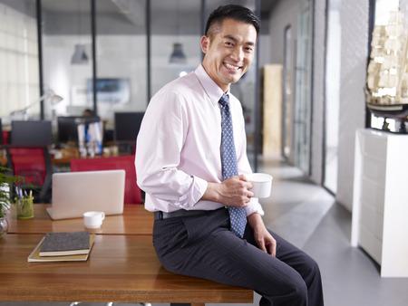 un homme d'affaires asiatique tenant tasse de café assis sur le bureau dans le bureau, souriant et joyeux.
