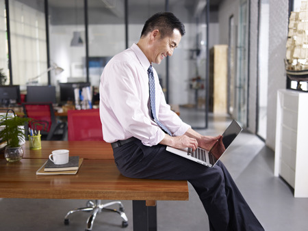 an asian businessman sitting on desk using laptop computer in office, happy and smiling, side view.