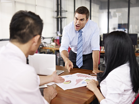 anger management: bad-tempered caucasian business executive yelling at two asian subordinates in office. Stock Photo