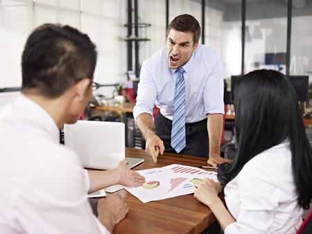 mauvaise humeur dirigeant d'entreprise caucasien crier à deux subordonnés asiatiques dans le bureau. Banque d'images